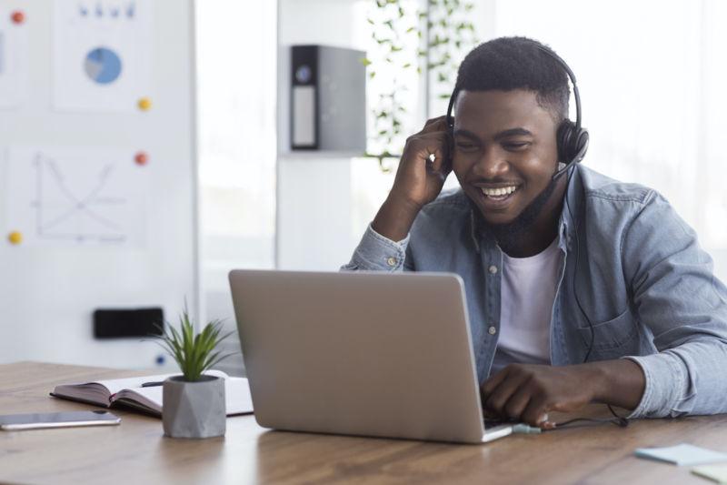 Cheerful african american worker wearing headphones, watching webinar on laptop in office